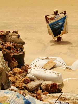 Vendedor observa destroços de calçada na Ponta Negra (Foto: G1)