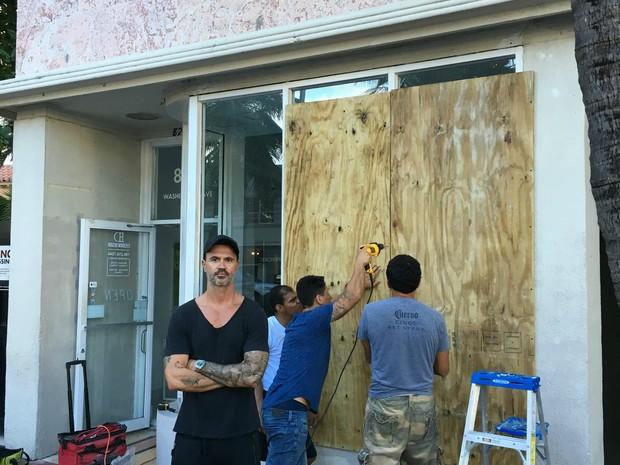 Empresário Renato Mendonça protege sua loja com tapumes temendo efeitos do furação (Foto: Arquivo pessoal/BBC)