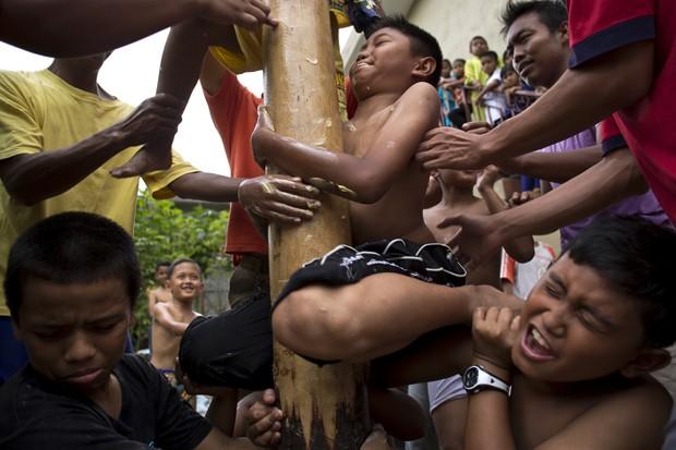 Grupo se esforça para tentar subir em pau de sebo durante competição na Malásia (Foto: Mohd Rasfan/AFP)