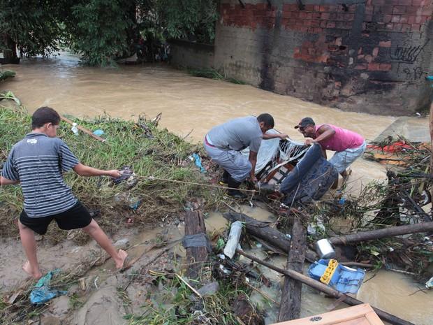 Moradores fazem um multitrão para desobistruir um corrego que corta Santa Rita que estava cheio de moveis levado pela chuva. (Foto: Cléber Júnior/ Extra/O Globo)