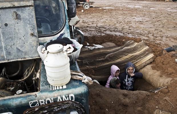 Em foto de 22 de novembro, crianças aparecem em trincheira construída para proteção contra os ataques do grupo Estado Isolâmico em Kobane (Foto: Jake Simkin/AP)