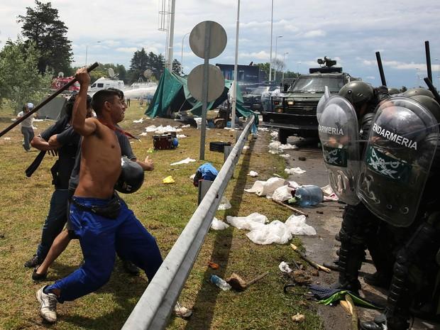 Manifestantes que bloqueavam a principal entrada do aeroporto internacional Ezeiza, em Buenos Aires, entram em confronto com policiais na terça (22) (Foto: La Nacion/Anibal Greco via AP)