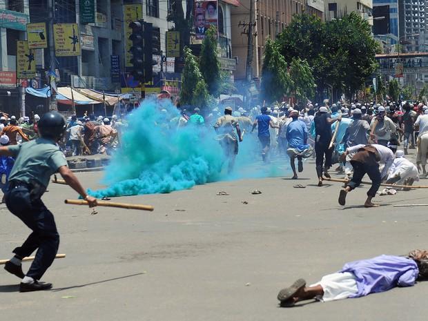 Manifestantes islâmicos correm enquanto a polícia lança gás contra a multidão que protesta exigindo uma lei sobre blasfêmia em Bangladesh. (Foto: Munir Uz Zaman/AFP)