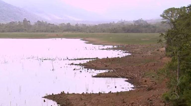 A água, que antes chegava na vegetação, baixou tanto que dá para ver as margens (Foto: Reprodução/RBS TV)