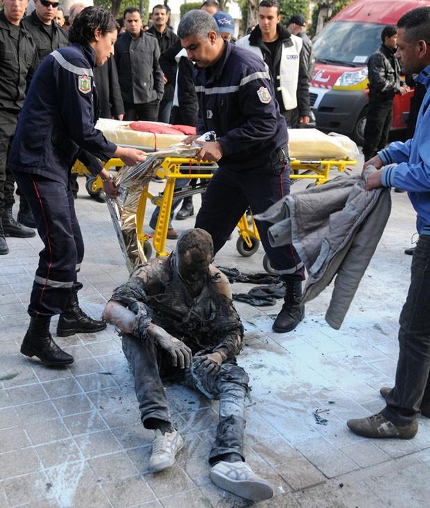 Bombeiros socorrem jovem que ateou fogo ao próprio corpo na Tunísia (Foto: Zine Tap/AP)