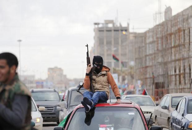Mascarado, Líbio celebra no topo de um veículo o segundo aniversário da revolução no país (Foto: Mohammad Hannon/AP)