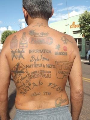 Edson Aparecido mostra as tatuagens de anúncio nas costas (Foto: Marcos Lavezo/G1)