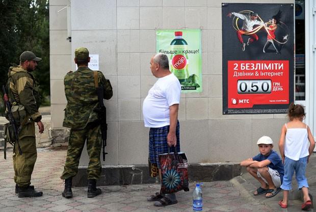 Cartaz com instruções para moradores é colocado por separatista em Novoazovsk nesta sexta-feira (29) (Foto: Francisco Leong/AFP)