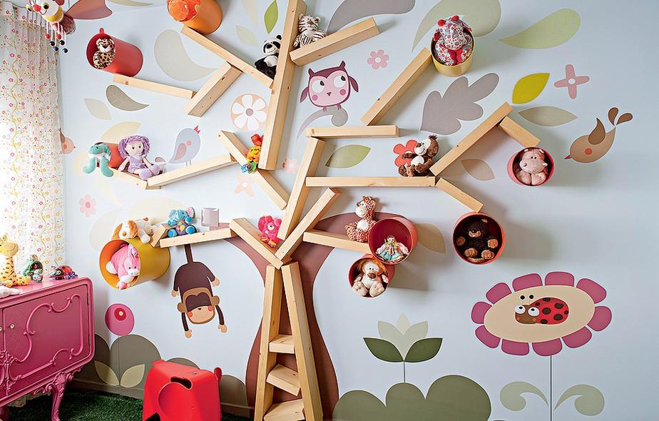 """Aqui, a criatividade deu o tom para o quarto, onde adesivos ajudaram a compor a estante em formato de árvore, que ocupa a parede inteira. Os """"galhos"""" que abrigam brinquedos são de madeira pínus. Criação do arquiteto Rodrigo Angulo"""