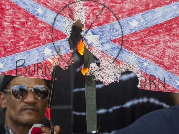 Um manifestante queima uma bandeira da Confederação durante um protesto em Los Angeles, na Califórnia. Os manifestantes apoiavam o governador da Carolina do Sul que removeu a bandeira da sede do governo (Foto: Ringo Chiu/Getty Images/AFP)