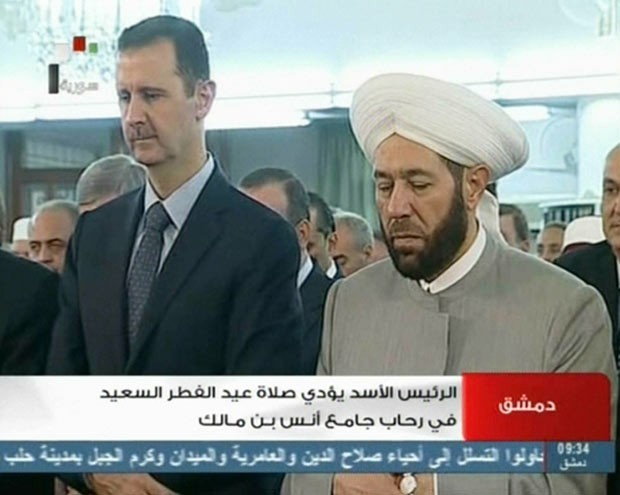 O presidente da Síria, Bashar al-Assad, reza ao lado do grande múfti da Síria, Ahmed Hassun, nesta quinta-feira (8) em Damasco (Foto: AP)
