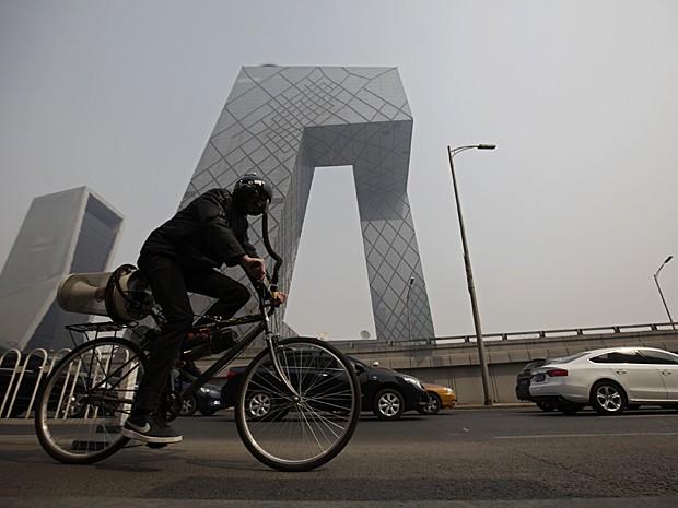 Matt Hope pedala pelas ruas de Pequim nesta terça-feira (26) (Foto: Petar Kujundzic/Reuters)