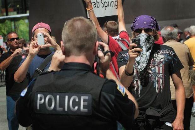 Policial filma maifestantes e é filmado de volta. Além dos enfermeiros, outros grupos como um braço do 'Ocupe Wall Street' também participaram do protesto, que ocorre no quinto dia seguido de manifestações aproveitando as atenções voltadas à cidade devido à reunião da Cúpúla da Otan no início da semana que vem, nos dias 20 e 21 de maio. (Foto: Scott Olson/Getty Images/AFP)
