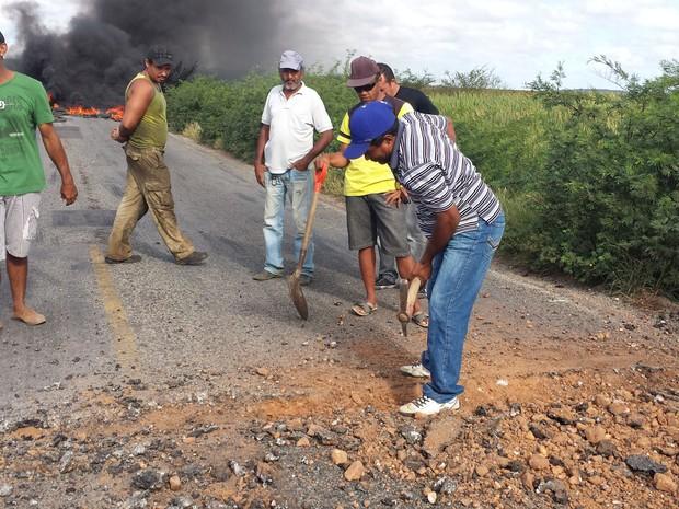 Moradores fazem a a quebra do pavimento da Rodovia  647. (Foto: Isa Mendes/TV Grande Rio)