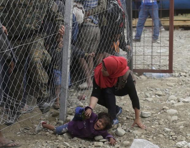 Policiais tentam conter imigrantes que queriam passar sob cerca para embarcar em trem na Macedônia nesta segunda-feira (7) (Foto: Stoyan Nenov/Reuters)