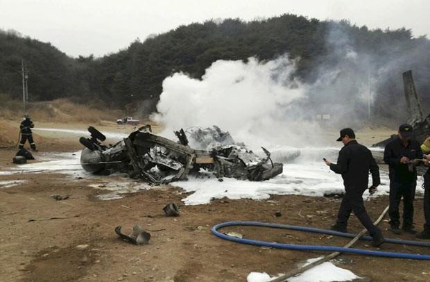 Bombeiros tentam extinguir fogo em helicóptero americano que caiu em Chulwon, na Coreia do Sul, nesta terça-feira (16) (Foto: Yonhap/AP)