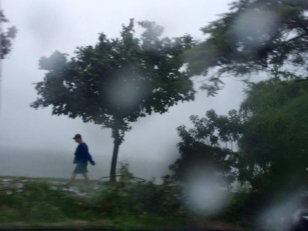 Homem caminha sob a chuva na Lagoa Rodrigo de Freitas (Foto: Kathia Melo/ G1)