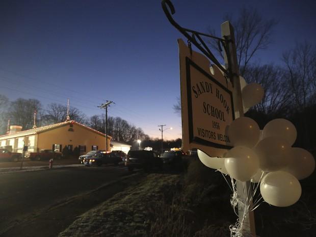 Balões brancos decoram placa que indica direção da escola Sandy Hook, na manhã deste sábado (Foto: AP)