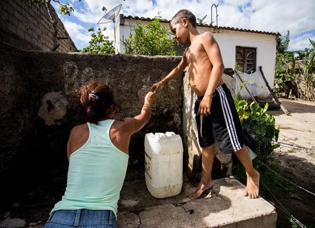 A dona de casa Creuza Gomes da Silva, 37, tenta buscar água no 'chafariz', uma torneira dividida por todos os vizinhos, com os filhos. Desta vez, voltou de mãos vazias (Foto: Jonathan Lins/G1 AL)