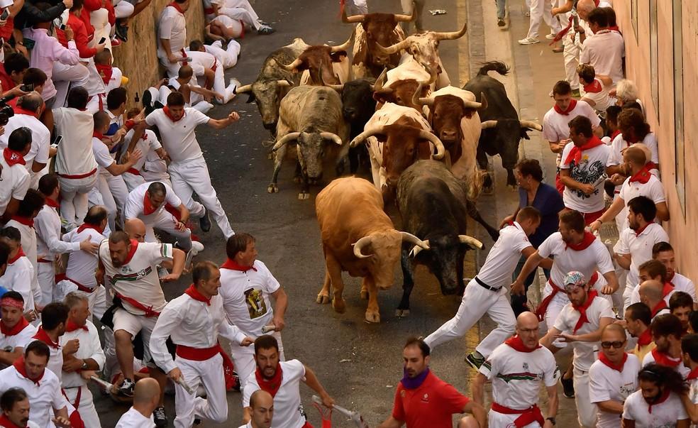 Participantes da corrida de touros em Pamplona, na Espanha, corem nesta sexta-feira (7)  (Foto: AP Foto/Alvaro Barrientos)