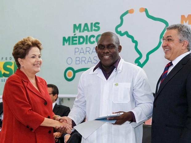 Presidente Dilma Rousseff, o médico cubano Juan Delgado e o Ministro da Saúde Alexandre Padilha durante sanção da lei que institui o Programa Mais Médicos.  (Foto: Roberto Stuckert Filho/PR)