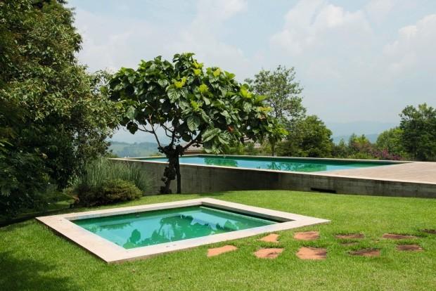 Jardim da frente Com um belo tom de verde, a piscina avança ao longo do declive do terreno. No canto dir., um spa com hidromassagem. No centro da foto, uma exuberante figueira-de-jardim (Foto: Cacá Bratke / Editora Globo)