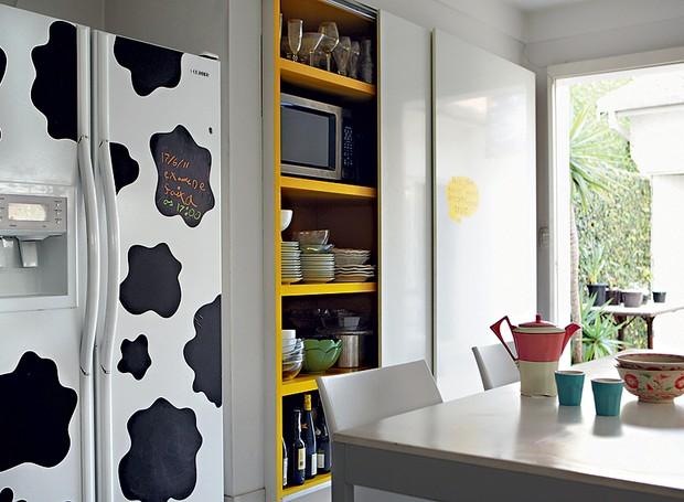 Por pura diversão, a arquiteta Fabiana Frattini cobriu a geladeira com adesivos de estampa de pele de vaca e pintou de amarelo o interior dos armários da cozinha (Foto: Edu Castello/Casa e Jardim)