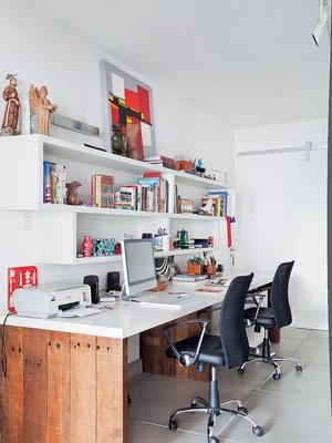 o hall de entrada deu lugar ao escritório do casal, que criou a mesa executada pela arthem Marcenaria. ela é mais larga para eles desenharem seus projetos. Separados nos nichos da estante ficam livros de arte, design, arquitetura, paisagismo e fotografia (Foto: Lufe Gomes)