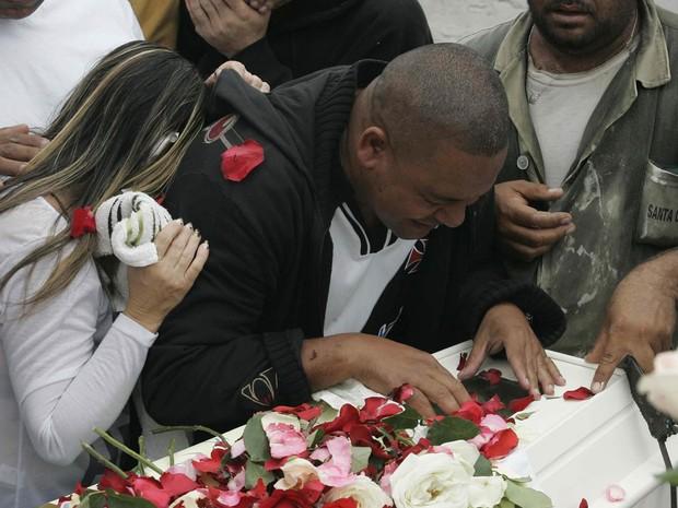 Homem se emociona sobre o caixão do menino Kayo da Silva Costa, de 8 anos, durante enterro no Cemitério do Murundu, em Padre Miguel, Zona Oeste do Rio de Janeiro. (Foto: Alessandro Costa/Agência O Dia/Estadão Conteúdo)