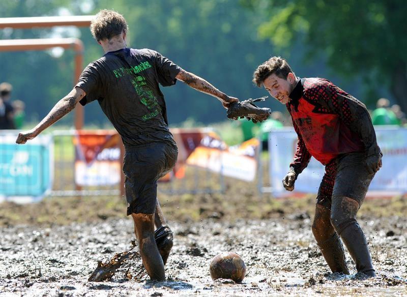Jogador perde o tênis durante campeonato de futebol na lama, na Alemanha
