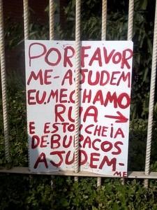 Placa colocada em rua com problemas no asfalto (Foto: Leon Botão/G1)
