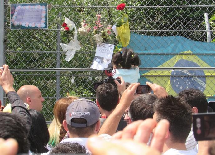 Criança coloca uma flor em homenagem a Ayrton Senna, na curva Tamburello, em Ímola (Foto: Felipe Siqueira)