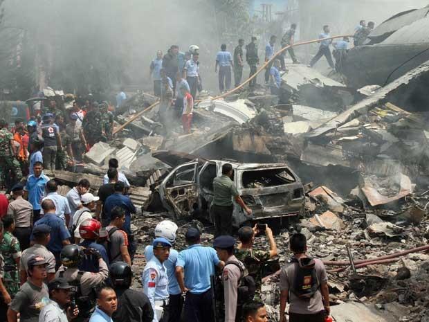 Bombeiros e militares inspecionam o local de queda de uma aeronave indonésia. (Foto: Gilbert Manullang / AP Photo)