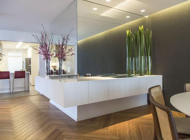 O espaço entre a sala de jantar e a cozinha ganhou móvel com espelhos desenhado pela arquiteta e executado pela AG Movelaria (Foto: Salvadore Bussacca/Divulgação)