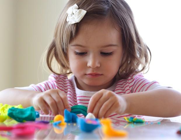 Criança brincando de massinha na mesa (Foto: Shutterstock)