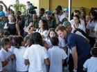 Harry chega ao Alemão, no Rio, e é saudado por coral de crianças