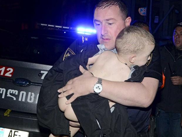 Socorrista carrega uma criança de uma casa inundada em Tbilisi. (Foto: Irakli Gedenidze / Reuters)