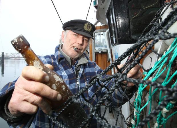 Konrad Fischer segura garrafa com mensagem jogada há 101 anos no mar da Alemanha (Foto: Uwe Paesler, DPA/AFP)