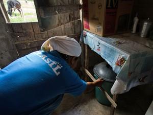 A agricultora Maria Madalena Ferreira Silva, 30, grávida, busca água na cabeça de duas a três vezes ao dia da cisterna da vizinha e guarda nos fundos da casa (Foto: Jonathan Lins/G1 AL)