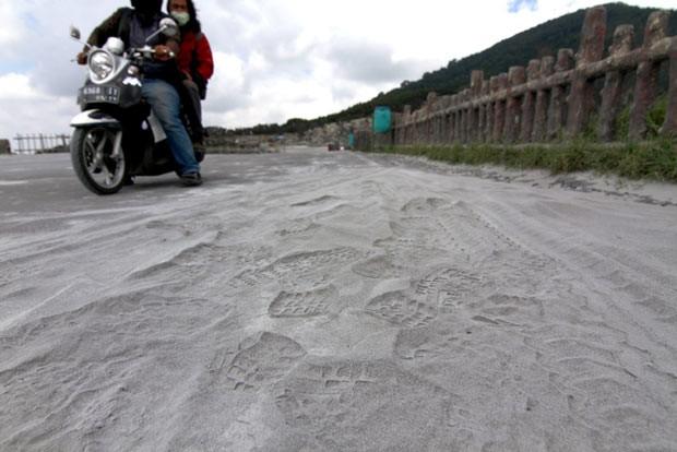 Moradores param moto para observar cinzas de vulcão nesta quinta-feira (7) em Java Ocidental (Foto: AP)