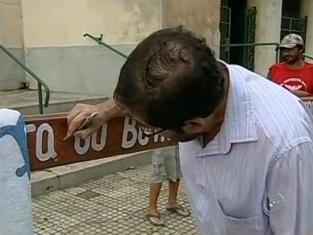 O funcionário público Benedito Luiz da Silva foi um dos primeiros fiéis católicos a deixar uma mensagem na madeira antes mesmo da partida do pagador de promessa. (Foto: Reprodução TV TEM)