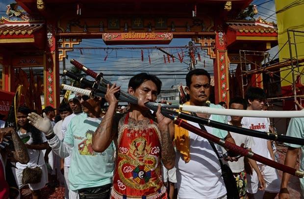 Homem caminha com espadas atravessadas por sua bochecha em Phuket (Foto: Christophe Archambault/AFP)