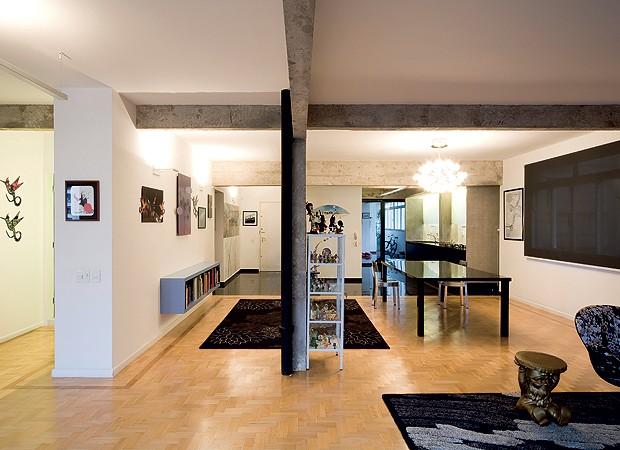 Restaurado na reforma, o assoalho original de peroba-rosa reveste quase todo o apartamento, até o hall de circulação e a sala de jantar (à dir.), com cadeiras de alumínio da Conceito Firma Casa (Foto: Maíra Acayaba)