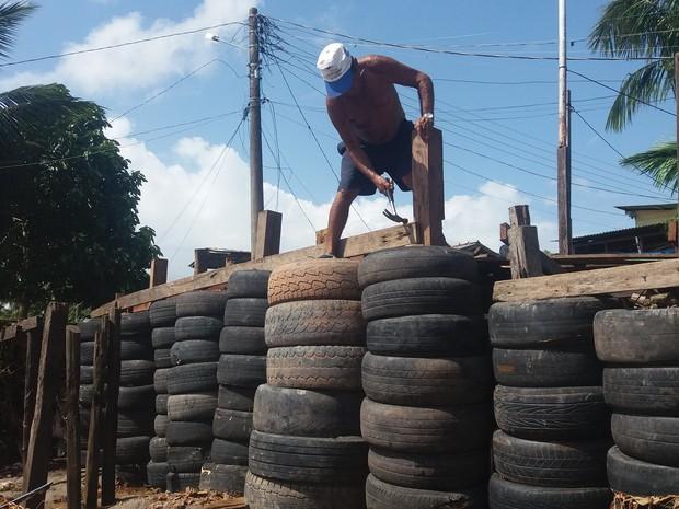 Adenor Sanches mora há 25 anos no Aturiá e ajuda na barreira de pneus (Foto: John Pacheco/G1)
