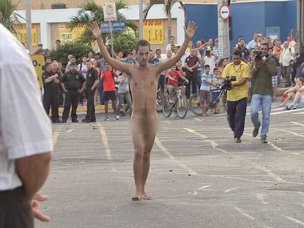 Manifestante de braços erguidos se aproximou da polícia e foi detido (Foto: TV Verdes Mares/Reprodução)