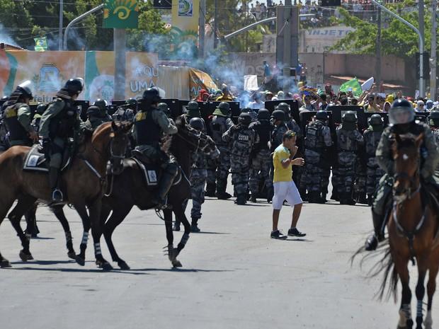 Homem que estava indo ao jogo da seleção brasileira em Fortaleza fica no meio da confusão em Polícia e manifestantes (Foto: Vanderlei Almeida/AFP)