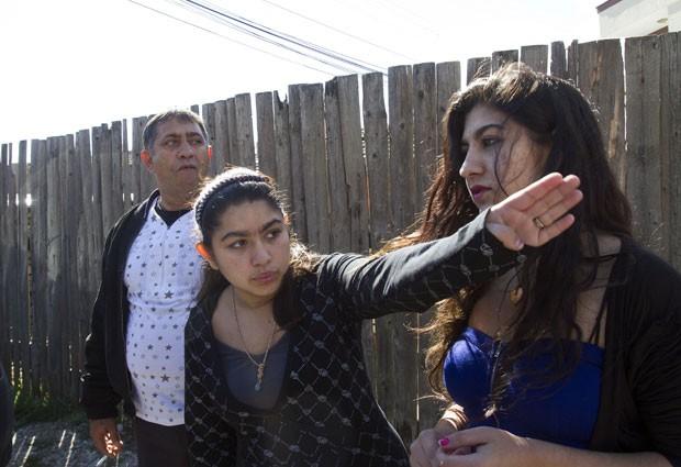 Leonarda Dibrani gesticula ao lado de sua irmã Maria, de 17 anos, e seu pai, Resat Dibrani (Foto: Visar Kryeziu/AP)