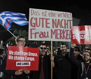 Jovens gregos comemoram a vitória de Alexis Tsipras em Atenas, no domingo, dia 25, e empunham cartazes provocando a Alemanha e a chanceler alemã Angela Merkel, a maior defensora da austeridade fiscal na Europa (Foto: ASSOCIATED PRESSAP)