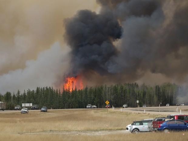 Motoristas em comboio deixam região afetada por incêndio em Fort McMurray, em Alberta, no Canadá, na sexta (6) (Foto: Cole Burston/AFP)