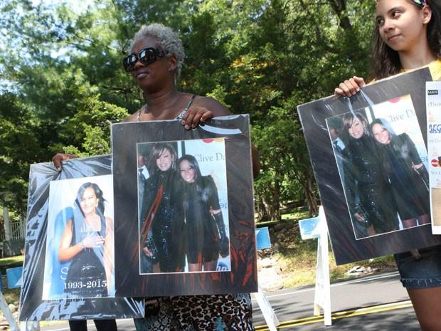 Fãs seguram fotos de Whitney Houston e Bobbi Kristina Brown do lado de fora do Fairview Cemetery, em Nova Jersey, nesta segunda-feira (3); a filha única da cantora foi enterrada ao lado da mãe  (Foto: Thomas E. Franklin/The Record/AP )